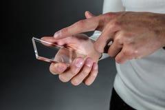 Mains tenant le téléphone transparent futuriste Photo stock