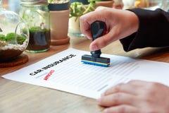 Mains tenant le tampon en caoutchouc avec l'assurance auto approuvée sur en bois Photo libre de droits