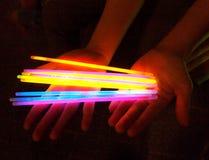Mains tenant les bâtons colorés de lueur Photographie stock libre de droits