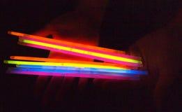 Mains tenant les bâtons colorés de lueur Photo stock