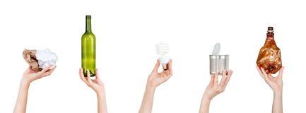 Mains tenant les bouteilles chiffonnées de papier, d'ampoule, en verre et de plastique, boîte en fer blanc d'isolement sur le fon photo libre de droits
