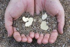 Mains tenant les formes et le sable de coeur Images libres de droits