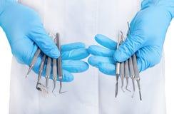 Mains tenant les instruments dentaires photographie stock