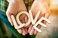 Mains tenant les lettres en bois avec amour de mot Photos stock
