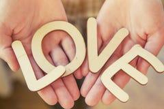 Mains tenant les lettres en bois avec amour de mot Photographie stock libre de droits