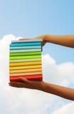 Mains tenant les livres durs colorés de couverture images libres de droits