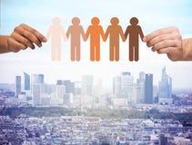Mains tenant les personnes multiraciales à chaînes de papier Image stock