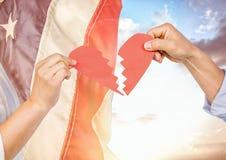 Mains tenant un coeur brisé contre le drapeau américain de flottement Photos libres de droits