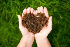 Mains tenant un coeur de la terre sur le fond vert naturel Ecolog Image libre de droits