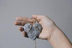 Mains tenant un coeur en pierre dans l'esclavage de jute sur le fond gris Images libres de droits