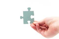 Mains tenant un morceau de puzzle Photographie stock libre de droits