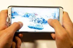 Mains tenant un smartphone sur lequel le jeu, monde gameplay de Gameplay d'attaque éclaire de réservoirs image stock