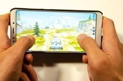 Mains tenant un smartphone sur lequel le jeu, monde gameplay de Gameplay d'attaque éclaire de réservoirs image libre de droits