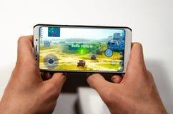 Mains tenant un smartphone sur lequel le jeu, monde gameplay de Gameplay d'attaque éclaire de réservoirs photos stock