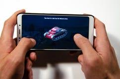 Mains tenant un smartphone sur lequel le jeu, monde gameplay de Gameplay d'attaque éclaire de réservoirs photos libres de droits