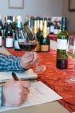 Mains tenant un verre à vin et un stylo pour l'échantillon de vin Photos stock