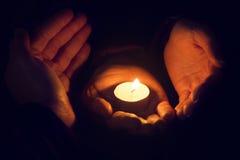 Mains tenant une bougie brûlante dans l'obscurité Photo stock