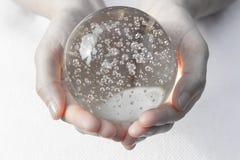 Mains tenant une boule de cristal image libre de droits