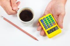 Mains tenant une calculatrice et une tasse de café sur le fond blanc photos libres de droits
