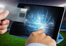 Mains tenant une carte de crédit et touchant l'écran d'un comprimé devant le champ d'herbe Photos stock
