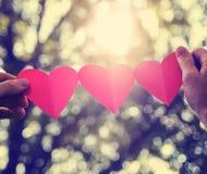 Mains tenant une ficelle des coeurs de papier jusqu'au soleil pendant les soleils Photos stock
