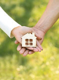 mains tenant une maison en bois Image stock