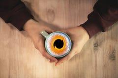 Mains tenant une tasse avec la mer photo libre de droits