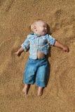 Mains tendues menteuses de bébé blanc heureux sur le grain Photos stock