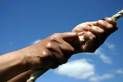 Mains tirant sur la corde Photographie stock libre de droits