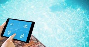 Mains touchant des icônes sur l'écran numérique du comprimé par la piscine image stock