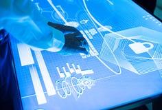 Mains touchant sur une table de l'espace de cyber au système débloqué Image libre de droits