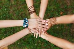 Mains unies de plan rapproché d'amies, jeunes filles dans des bracelets de boho Images libres de droits