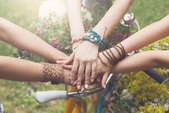 Mains unies de plan rapproché d'amies, jeunes filles dans des bracelets de boho Photographie stock libre de droits
