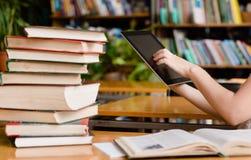 Mains utilisant la tablette dans la bibliothèque photos libres de droits
