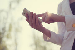 Mains utilisant le smartphone Photos stock