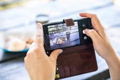 Mains utilisant un téléphone pour prendre la photo du dessert et d'une tasse de Dr. chaud Image libre de droits