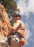 Maintain Climber / Rock. Happy young male rock climber hanging on ropes sitting in harnas with ropes and huit with figure eight descenders and carabiners Stock Photos
