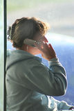 Maintain Contact. A young woman talks on her cell phone while waiting for her plane to board royalty free stock images
