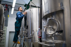 Maintained worker working at brewery. Attentive maintained worker working at brewery stock photos