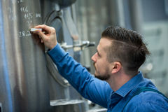 Maintained worker writing on tank. Attentive maintained worker writing on tank at brewery royalty free stock photography