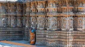 Maintaining ancient appearances in India. Karnataka, India - March 2, 2018: Attendant brushing crevices in intricately carved walls of the 13th century Stock Image