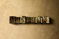 MAINTAINING - close-up of grungy vintage typeset word on metal backdrop. Royalty free stock illustration.  Can be used for online banner ads and direct mail Stock Images