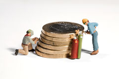 Maintaining The Euro. Miniature model workmen maintaining a pile of Euro coins with powertools and acetylene welding Royalty Free Stock Photo