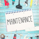 Maintenance  against tools and notepad on wooden background Royalty Free Stock Images