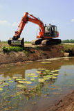 Maintenance ditches by dredger. A caterpillar is cleaning up a ditch for right discharge of water Stock Images