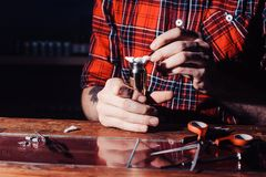 The process of servicing the mechanical vape device. Master replace wire for smoking. Ecig rapairing process. Maintenance of electronic mech mod vaping device stock image