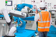 Maintenance engineer control automatic robotic hand machine tool. At industrial manufacture factory Royalty Free Stock Photo
