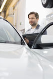 Maintenance engineer holding tablet PC while examining car in repair shop Stock Photo