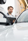 Maintenance engineer holding tablet PC while examining car in repair shop Stock Images