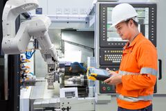 Maintenance engineer programing automated robotic with CNC Royalty Free Stock Images